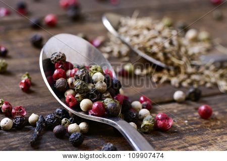 closeup of a spoon with a variety of different peppercorns, such as pink pepper, black pepper, red pepper or white pepper, on a rustic wooden table