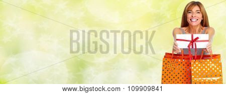 Shopping woman with envelope and gifts over green background.