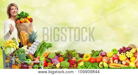Senior woman with vegetables over green background. Healthy diet.