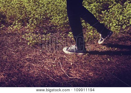 Feet In Sneakers Walking In The Forest. Vintage Tone.