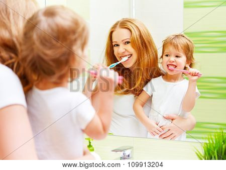 Happy Family Mother And Daughter Child Brushing Her Teeth Toothbrushes