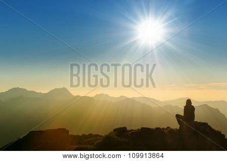 lonely sad person sitting on mountain summit at dawn