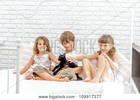 three little happy kids playing with black cat on white bed at home