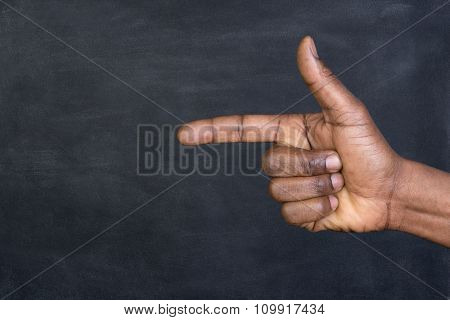 Male hand pointing a finger at copy space on a blackboard