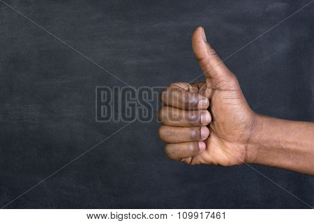 Thumbs up in front of a blackboard with copy space