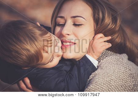 his mom is his greatest love, son and mom kissing and hugging, autumn day in park, closeup, selective focus