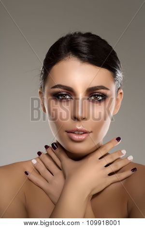 Beautiful model woman in beauty salon makeup Young modern girl in luxurious spa Lady make up Mascara for long lashes lipstick on lips eye shadow shiny hair manicure with nail polish Products Treatment