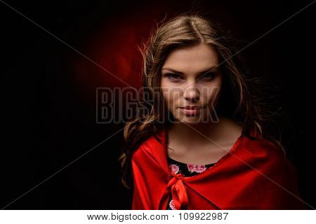 beautiful woman with red cloak in studio