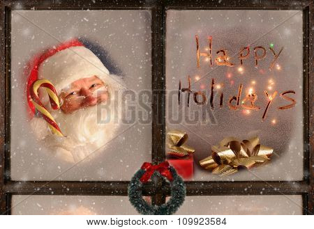 Santa Claus seen through a frosted window holding up a large old fashioned candy cane. Another pane has Happy Holidays and presents.