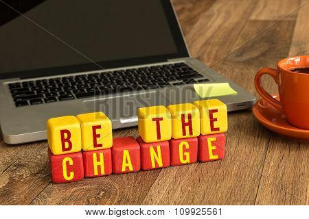 Be the Change written on a wooden cube in a office desk