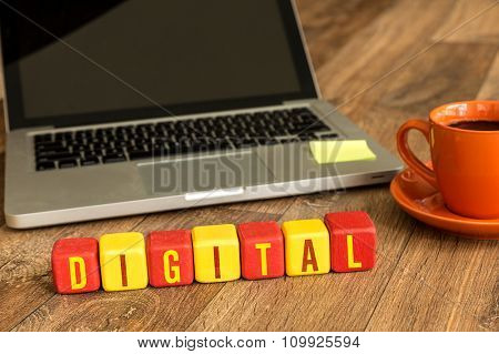 Digital written on a wooden cube in a office desk
