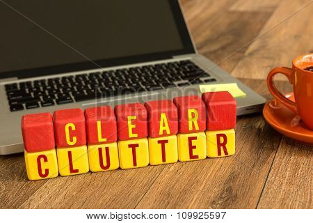 Clear Clutter written on a wooden cube in a office desk