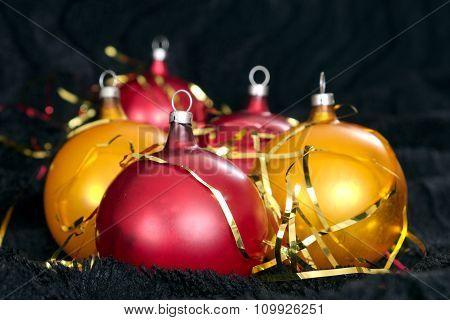 Red And Yellow Christmas Balls On A Black Backdrop