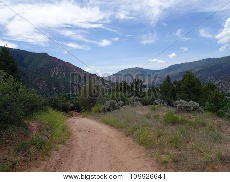 Dirt Path In The Forest Leading Down The Mountains