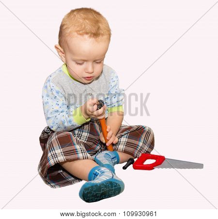 The Little Boy Plays With Plastic Instrumentamizh A Hammer And A Saw. The Isolated Picture On A Whit