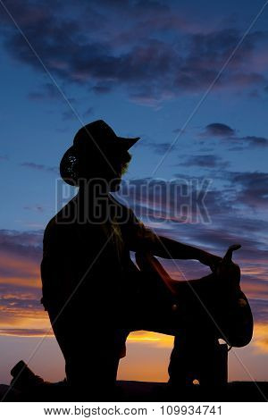 Silhouette Of Man Kneel With Saddle On Knee