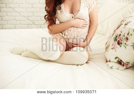 Pregnant on the bed in light room