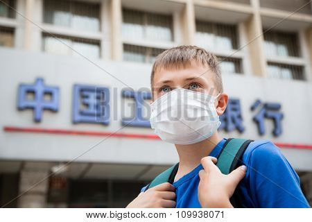 BEIJING - CIRCA JUNE , 2015: European boy in a protective mask on a street in Beijing. In Beijing, many days of the year hanging heavy smog from industrial enterprises.