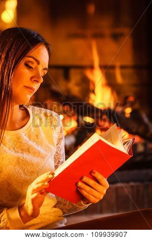 Woman Reading Book At Fireplace. Winter Home Relax