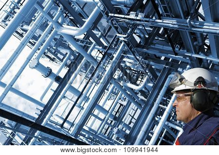oil and gas worker with large pipelines constructions, inside refinery details