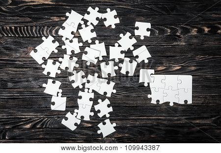 white puzzle pieces isolated on dark wooden table
