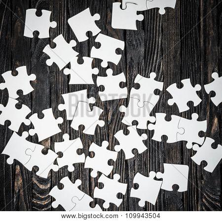 white puzzle pieces on dark wooden background