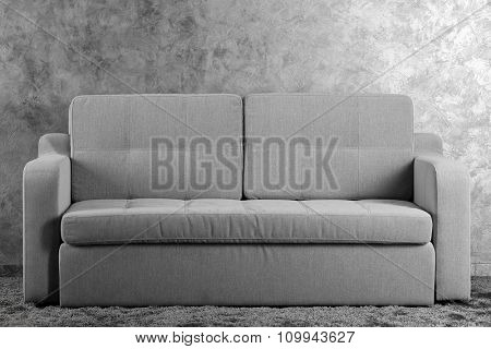 Comfortable sofa on grey wall background