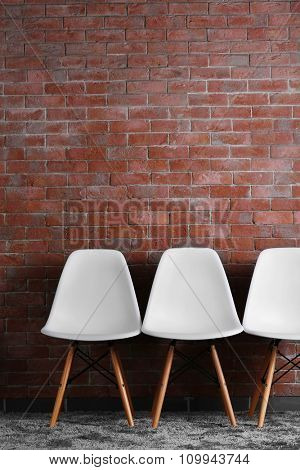 White modern chairs on brick wall background