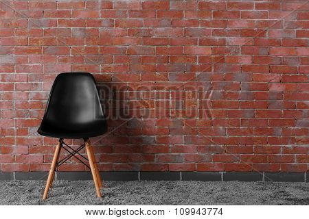 Black modern chair on brick wall background