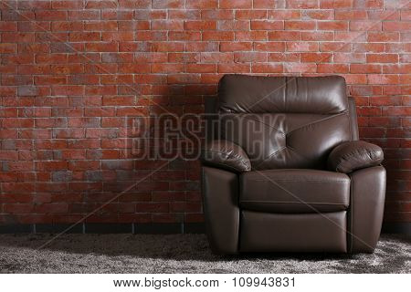 Brown leather chair on brick  wall background