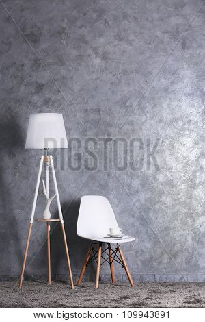 Stylish conception with chair and lamp on grey background