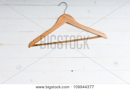 wooden clothes hanger on white wooden background