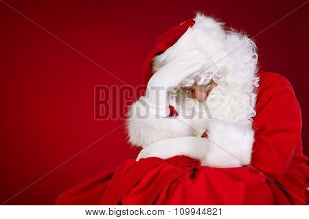 Sad Santa Claus holding head in hands and keeping eyes