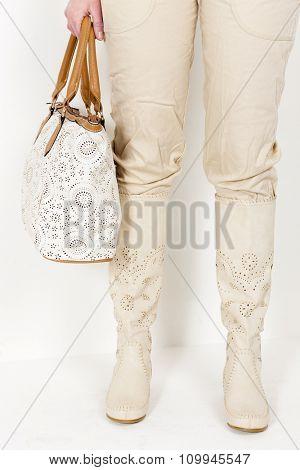 detail of standing woman wearing summer boots holding a handbag