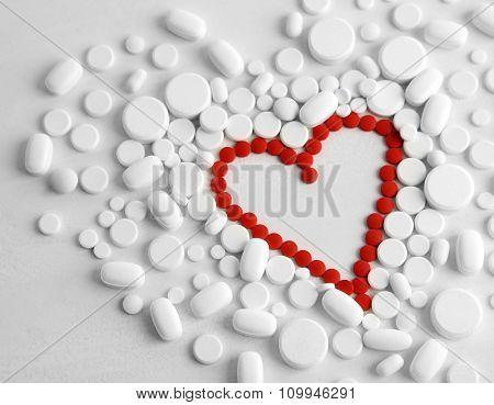 Heart of red pills on white pills background