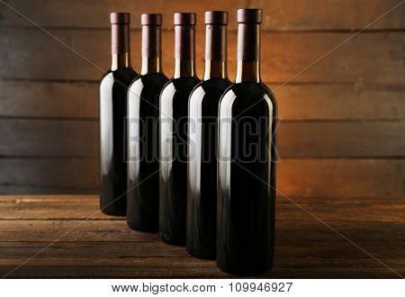Wine bottles in a row on the table against wooden background