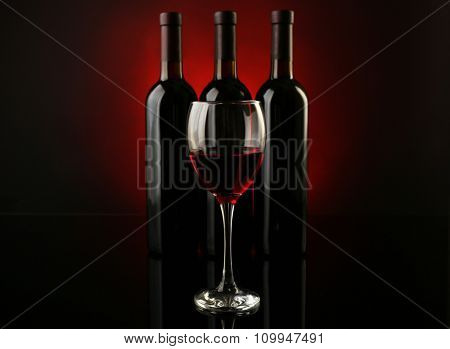 Wine glass against bottles in a row on dark red background, close up