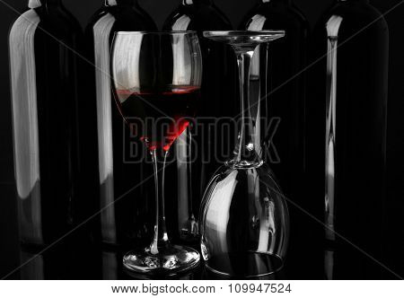 Wine glasses against bottles in a row on black background, close up