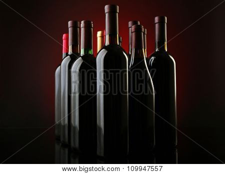 Wine bottles in a row on dark red background, close up