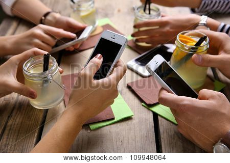Four hands with smart phones holding cocktails, on wooden table background