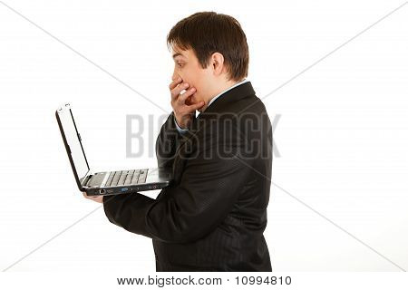 Shocked modern businessman looking in laptops screen