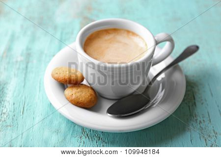 Cup of coffee on color wooden background