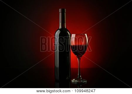 Wine glass and bottle on dark red background, close up