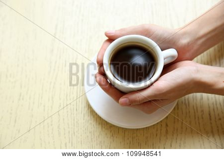 Cup of coffee with hands on table background