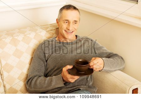 Mature man sitting on couch with cup of coffee.