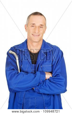 Mature repairman with folded arms holding wrench.