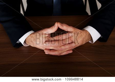 Mature businessman clenched hands on the desk.