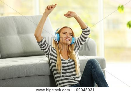 Yong woman sitting on the floor and listening to music