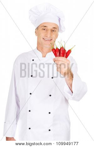 Male chef in uniform holding chilli peppers
