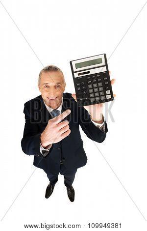 Mature businessman pointing on calculator.